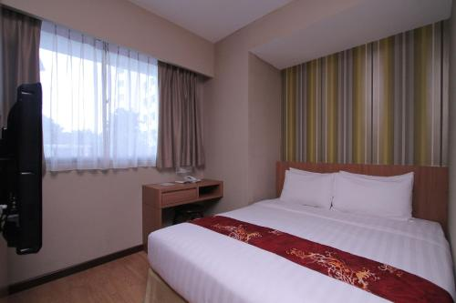 A bed or beds in a room at Likas Square Serviced Apartment