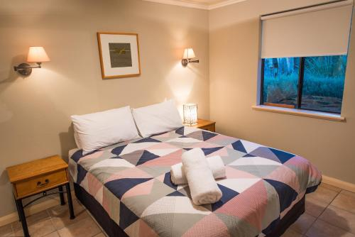 A bed or beds in a room at Whalers Cove Villas