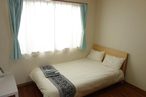 Okinawa Naha Rakuraku Houseにあるベッド