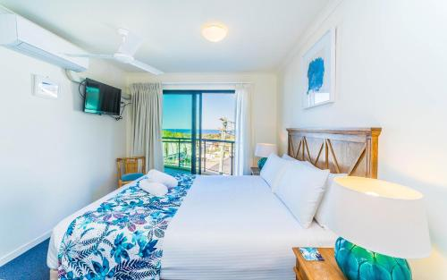A bed or beds in a room at The Cove Yamba