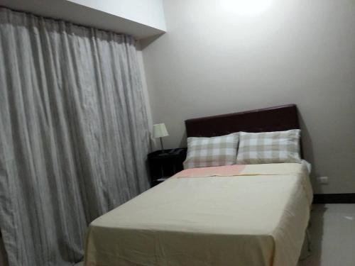 A bed or beds in a room at Ness Apartment at Manhattan Heights Cubao