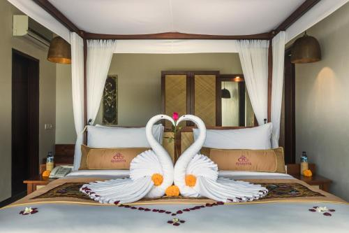 A bed or beds in a room at Ayuterra Resort