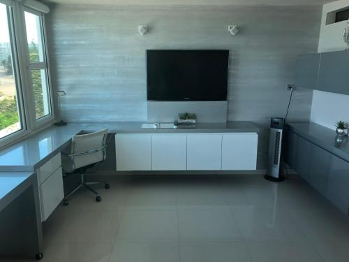 A television and/or entertainment center at Amapola SeaSide Beach Front Apartment