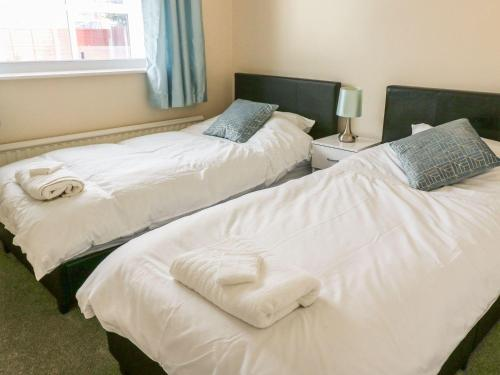 A bed or beds in a room at Rossall Beach Cottage, Fleetwood