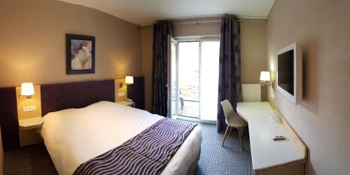 A bed or beds in a room at Hotel Les Remparts