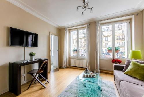 A television and/or entertainment center at Central Marais Lovely Apartment