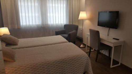 A bed or beds in a room at Apartamentos Centro Colón