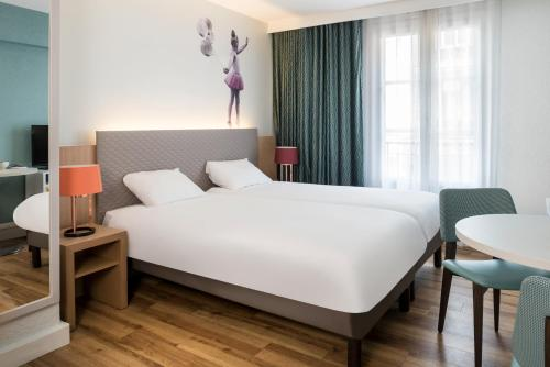 A bed or beds in a room at Aparthotel Adagio Paris Montmartre