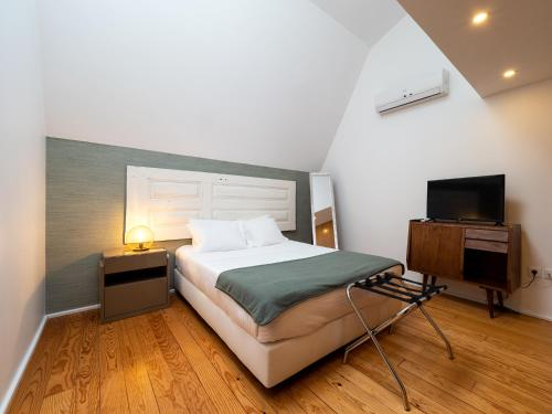 A bed or beds in a room at APA M - Loft Guesthouse Jardim das Maes Charming