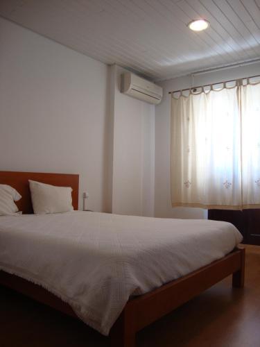 A bed or beds in a room at Pensão Aliança