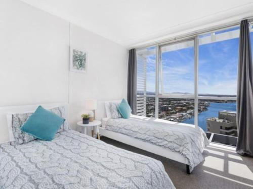 A bed or beds in a room at Beach Stay - Ocean & Riverview resort Chevron Renaissance central Surfers Paradise