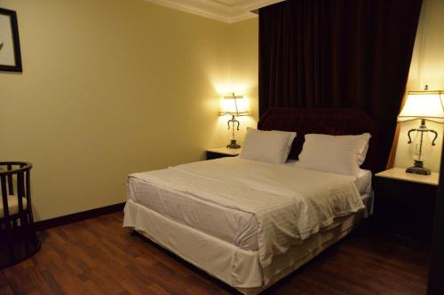 A bed or beds in a room at The Palace Suites