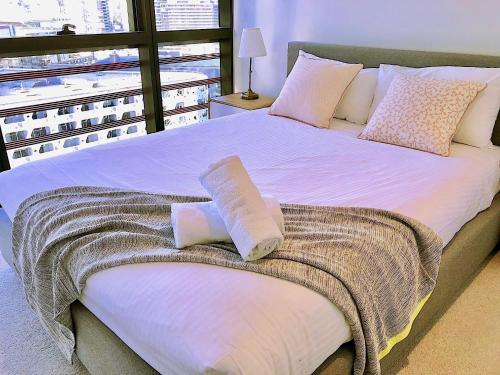 A bed or beds in a room at Pride Docklands Waterfront Apartment City View