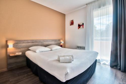 Un ou plusieurs lits dans un hébergement de l'établissement Zenitude Hôtel-Résidences Toulouse Métropole