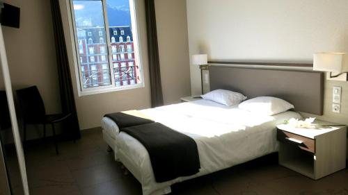 A bed or beds in a room at Appart'hotel le Pèlerin