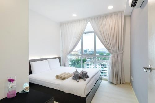 A bed or beds in a room at Straits Garden Suites, Georgetown