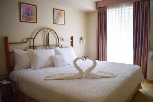 A bed or beds in a room at Suites Antique Apart Hotel