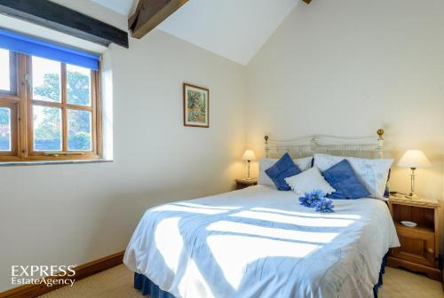 A bed or beds in a room at Highgrove Barns
