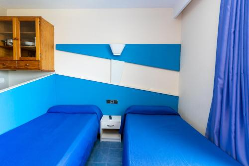 A bed or beds in a room at The Blue Apartments - Adults Only