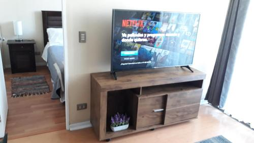 Una televisión o centro de entretenimiento en Central Apartment Santiago BYP