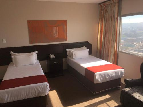 A bed or beds in a room at Coastlands Durban Self Catering Holiday Apartments
