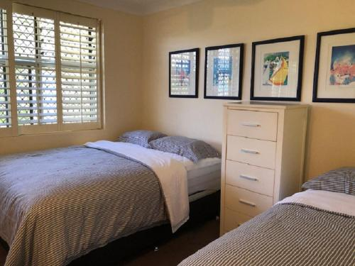 A bed or beds in a room at Frangipani 208