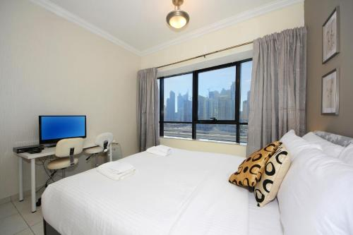 Signature Holiday Homes - Luxurious 1 Bedroom Apartment JLT, Dubai tesisinde bir odada yatak veya yataklar