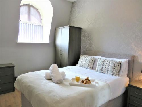 A bed or beds in a room at Comfort Stay Apartments Derby
