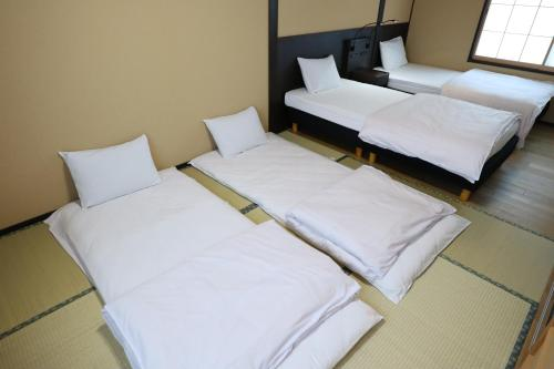 A bed or beds in a room at Kyoto Oyado ZEN