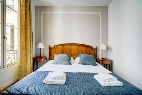 A bed or beds in a room at Apartments Du Louvre - Le Marais