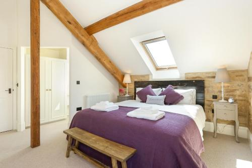 A bed or beds in a room at Classic Family Barn Conversion in Radcot