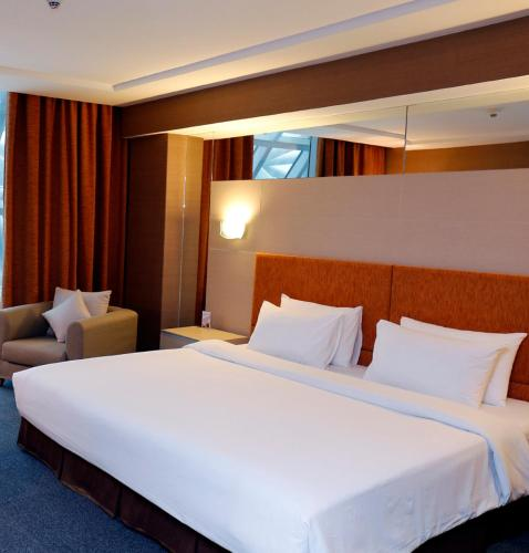 A bed or beds in a room at Miracle Transit Hotel