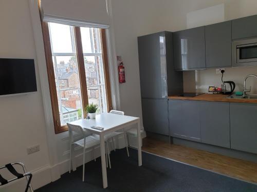 A kitchen or kitchenette at McMillan House Studio Apartments