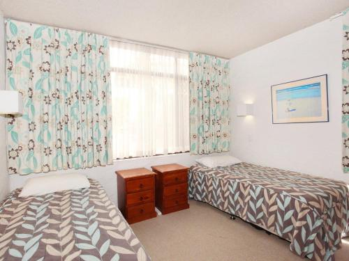 A bed or beds in a room at Warroo 3 - 2 BDRM Apt 100m to Alex Surf Beach