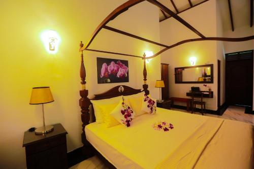 A bed or beds in a room at SRI LANKAN VILLA