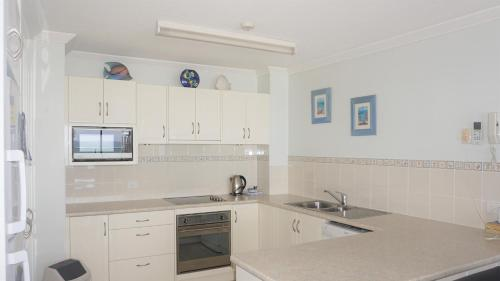 A kitchen or kitchenette at Pacific Surf Absolute Beachfront Apartments