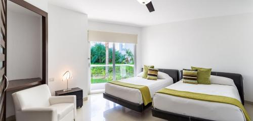 A bed or beds in a room at Mareazul Beach Front Resort Playa del Carmen