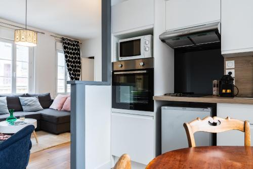 A kitchen or kitchenette at TOWNHOUSE TROUVILLE - Appart'Hotel & Studios