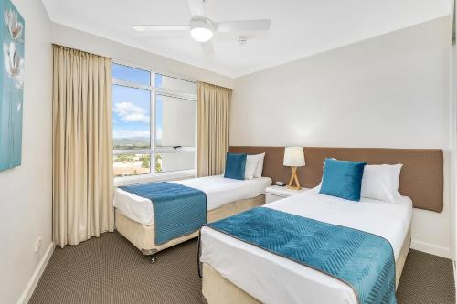 A bed or beds in a room at Burleigh Mediterranean Resort