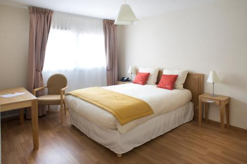 A bed or beds in a room at Domitys Les Clefs d'Or