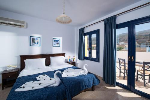A bed or beds in a room at Aegean Sky Hotel-Suites