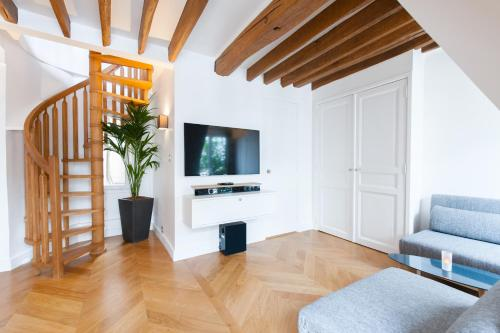 A television and/or entertainment center at Appartement de luxe, Opera-Louvre