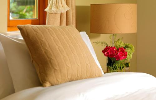 A bed or beds in a room at The Woodland Villas at Parknasilla Resort