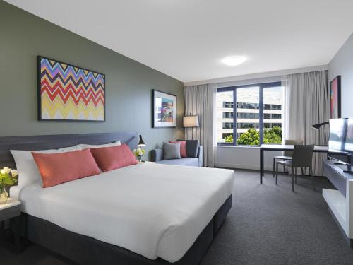 A bed or beds in a room at Adina Apartment Hotel Sydney Airport