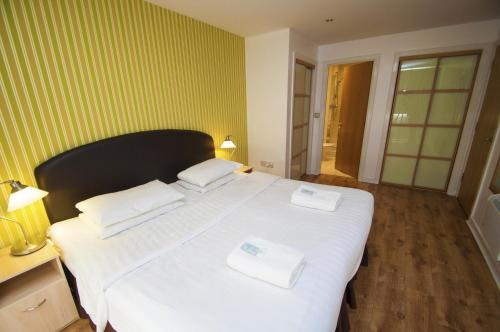 A bed or beds in a room at Ocean Serviced Apartments