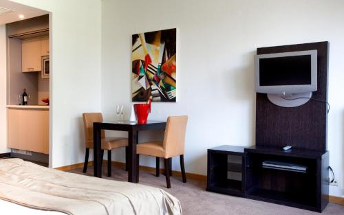 A television and/or entertainment center at Diamant Suites Brussels EU