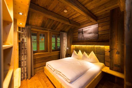 A bed or beds in a room at Chaletdorf Auszeit
