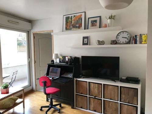A television and/or entertainment center at Mary's Apartment Parc des Expositions Porte de Versailles