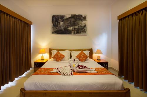 A bed or beds in a room at Sandi Agung Villa