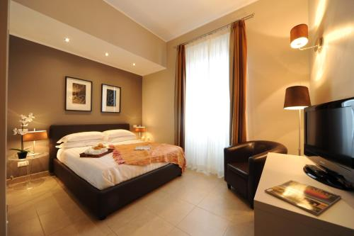 A bed or beds in a room at Trianon Borgo Pio Aparthotel